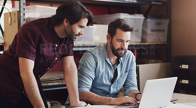 Buy stock photo Shot of two young businessmen using a laptop while designing a blueprint in a creative office