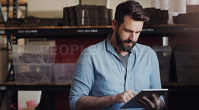 Buy stock photo Shot of a young businessman using a digital tablet in a creative office