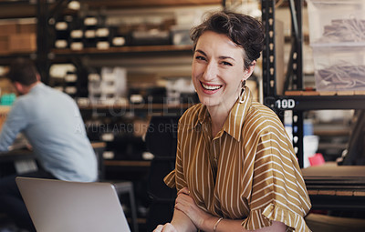 Buy stock photo Shot of a businesswoman using a laptop and smartphone in a creative office