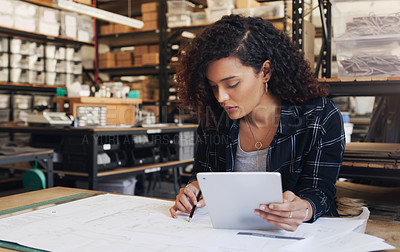 Buy stock photo Shot of a young businesswoman using a digital tablet while designing a blueprint in a creative office