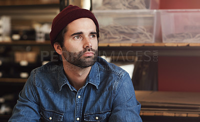 Buy stock photo Shot of a young businessman looking thoughtful in a creative office