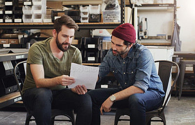 Buy stock photo Shot of two young businessmen reading a document in a creative office