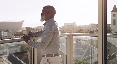 Buy stock photo Cropped shot of a contemplative senior man standing alone on his balcony and enjoying a cup of coffee
