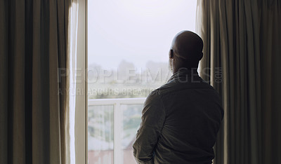 Buy stock photo Cropped shot of an unrecognizable man standing alone and looking out the window in his house during a day off
