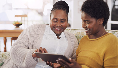 Buy stock photo Cropped shot of a happy young woman sitting with her senior mother and using a tablet in their living room
