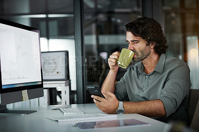 Buy stock photo Cropped shot of a handsome young businessman drinking coffee and using a cellphone while working in his office at night
