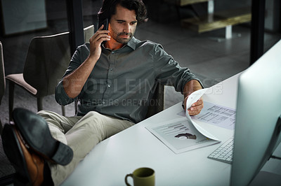 Buy stock photo Cropped shot of a handsome young businessman making phone calls and going over paperwork inside his office at night