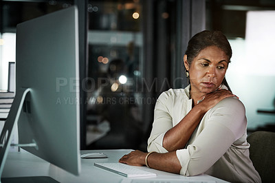 Buy stock photo Cropped shot of an attractive mature businesswoman suffering from shoulder pain while working inside her office at night