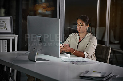 Buy stock photo Cropped shot of an attractive mature businesswoman using her cellphone while working inside her office at night