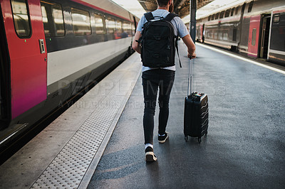 Buy stock photo Shot of a young man heading towards the train with his luggage