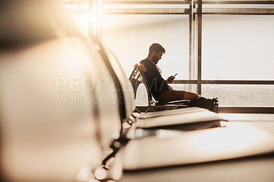 Buy stock photo Shot of a man using his cellphone while waiting for his flight at the airport