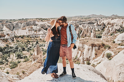 Buy stock photo Shot of a couple kissing while standing on a mountaintop
