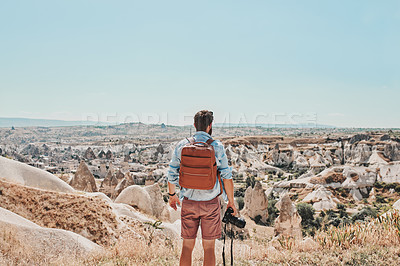 Buy stock photo Shot of a hiker holding his camera and backpack while standing on a mountaintop