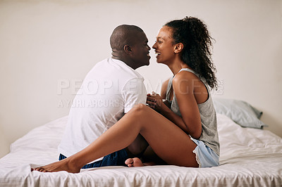 Buy stock photo Full length shot of an affectionate young couple smiling at each other in their bedroom at home