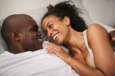 Buy stock photo High angle shot of an affectionate young couple smiling at each other while lying in bed at home