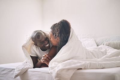 Buy stock photo Shot of an affectionate young couple sharing an intimate moment under the covers in their bedroom at home