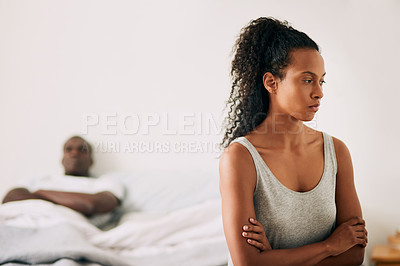 Buy stock photo Cropped shot of an attractive young woman looking upset while sitting on her bed with her husband in the background