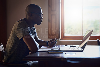 Buy stock photo Cropped shot of a handsome young businessman sitting alone at home and working on his laptop