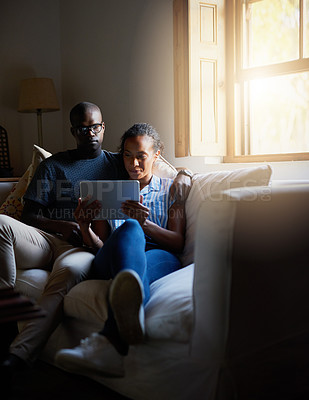 Buy stock photo Cropped shot of an affectionate young couple sitting together on the sofa and using a tablet