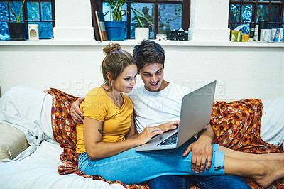 Buy stock photo Cropped shot of a cheerful young couple browsing on a laptop together while being seated on a sofa inside at home