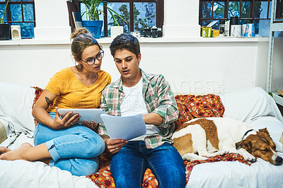 Buy stock photo Cropped shot of a cheerful young couple browsing on a digital tablet while doing paperwork on a sofa at home during the day