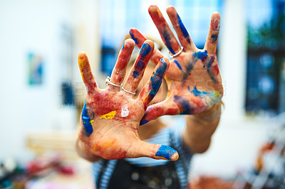 Buy stock photo Cropped shot of an unrecognizable female painter showing her paint-covered hands while standing in her art studio