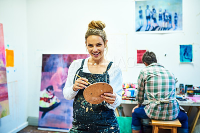 Buy stock photo Cropped portrait of an attractive young woman holding a palette and brush in art studio with her boyfriend in the background