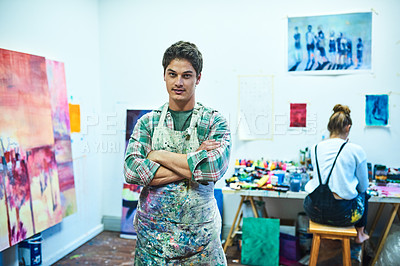 Buy stock photo Cropped portrait of a handsome young man standing with his arms crossed in an art studio with his girlfriend in the background