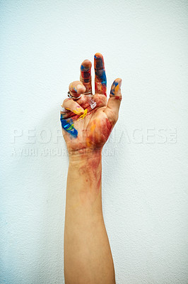 Buy stock photo Cropped shot of an unrecognizable female painter's paint-covered hand against a grey background