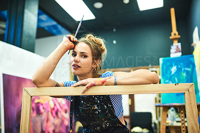 Buy stock photo Cropped portrait of an attractive young female painter leaning on a wooden frame while sitting in her art studio