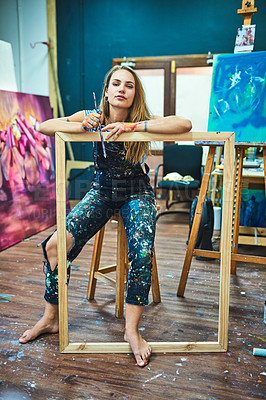 Buy stock photo Full length portrait of an attractive young female painter leaning on a wooden frame while sitting in her art studio