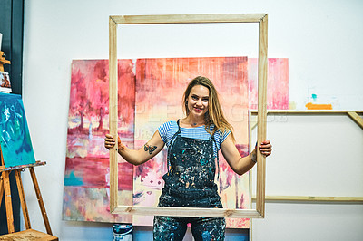 Buy stock photo Cropped portrait of an attractive young woman standing alone and holding a wooden frame in her art studio