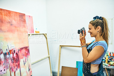 Buy stock photo Cropped shot of an attractive young woman standing and taking pictures of her art in her studio with a camera