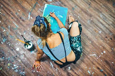 Buy stock photo High angle shot of an unrecognizable woman sitting and painting on the floor of her art studio
