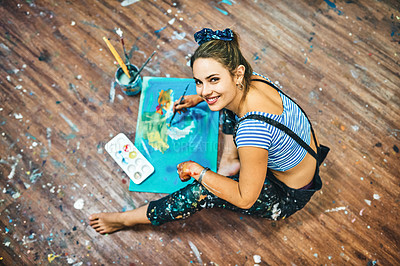 Buy stock photo High angle portrait of an attractive young woman sitting and painting on the floor of her art studio