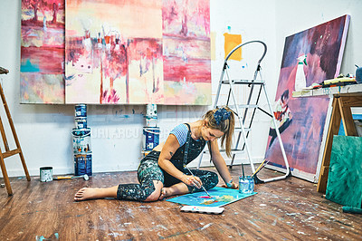 Buy stock photo Full length shot of an attractive young woman sitting and painting on the floor of her art studio