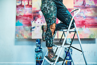 Buy stock photo Cropped shot of an unrecognizable woman standing on a ladder during a painting session in her studio