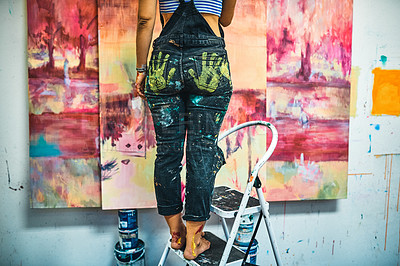 Buy stock photo Cropped shot of an unrecognizable woman standing on a ladder and painting in her art studio