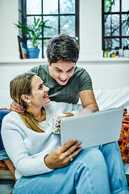 Buy stock photo Cropped shot of a happy young couple using a digital tablet while spending time together at home