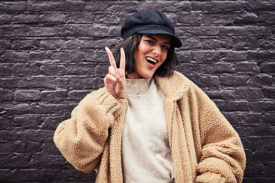 Buy stock photo Shot of a beautiful young woman making a peace gesture against a grey wall in the city