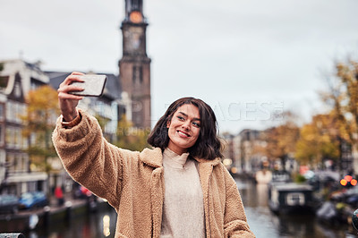 Buy stock photo Shot of a beautiful young woman taking a selfie while out and about in the city