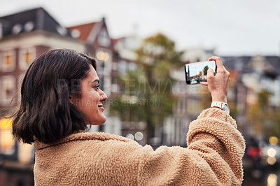 Buy stock photo Shot of a young woman taking pictures on a smartphone while out in the city
