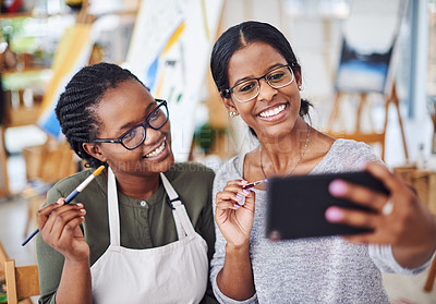 Buy stock photo Cropped shot of two young women taking a selfie while painting in a art studio