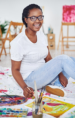 Buy stock photo Shot of a young woman sitting on the floor while painting in a art studio