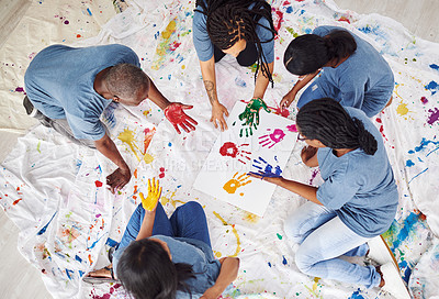 Buy stock photo Shot of a group of people of people leaving painted handprints on a white poster