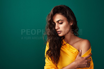 Buy stock photo Shot of a beautiful young woman posing against a coloured background