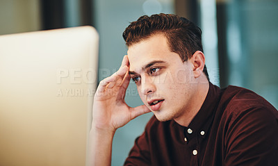 Buy stock photo Cropped shot of a handsome young businessman looking stressed while working on his computer in the office