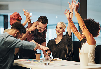 Buy stock photo Cropped shot of a group of young businesspeople with their hands in a huddle during a meeting in the office
