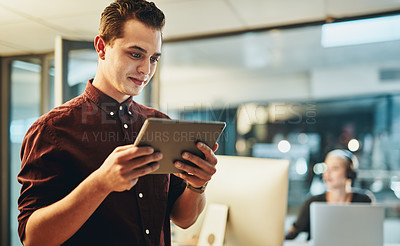 Buy stock photo Cropped shot of a handsome young businessman working on his tablet in the office