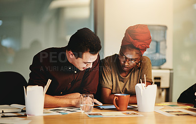 Buy stock photo Cropped shot of two young businesspeople working together on a tablet in their office